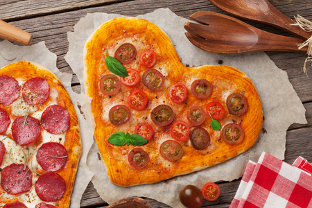 Heart shaped pizza with tomatoes and mozzarella. Valentines day greeting card. Top view