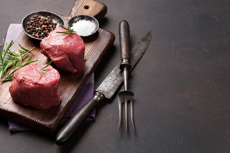 Raw fillet steak cooking on stone table. With space for your text Standard-Bild