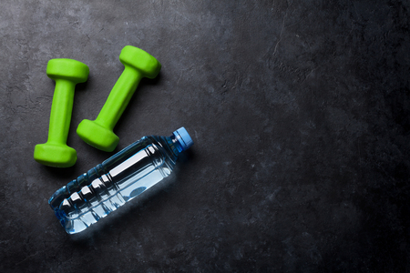 Fitness concept background with dumbbells and water bottle. Top view with space for your text