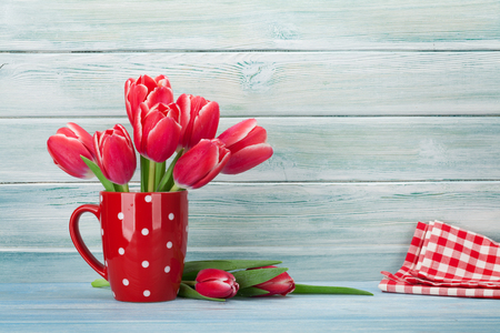 Red tulip flowers bouquet in cup in front of wooden wall.  Easter or Valentines day greeting card. With space for your greetings Standard-Bild