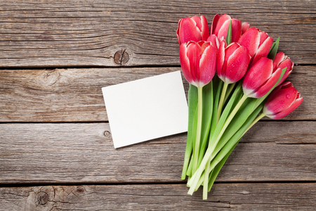 Red tulip flowers bouquet on wooden background. Easter or Valentines day greeting card. Top view with space for your greetings
