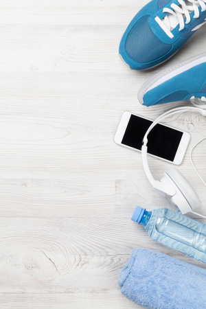 Fitness concept background with sneakers, headphones, water bottle and towel. Top view with space for your text Standard-Bild