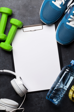 Fitness concept background with sneakers, headphones, dumbbells, water bottle. Top view with space for your text Standard-Bild