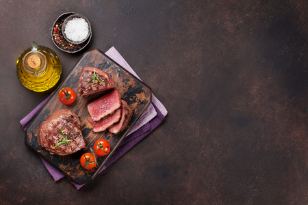 Grilled fillet steaks on cutting board. Top view with space for your text Standard-Bild
