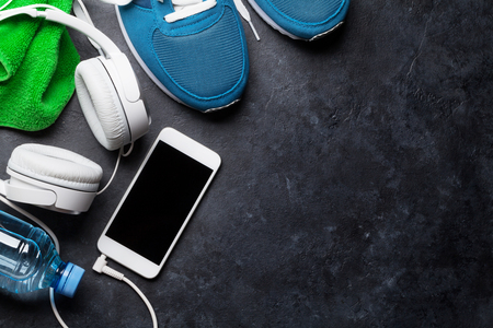 Fitness concept background with sneakers, headphones, smartphone, water bottle and towel. Top view with space for your text