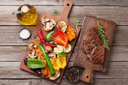 Grilled vegetables and beef steak on cutting board on wooden table. Top view Standard-Bild