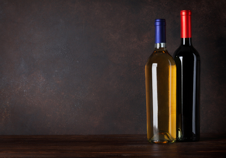 Red and white wine bottles in front of blackboard wall. With copy space for your text Standard-Bild