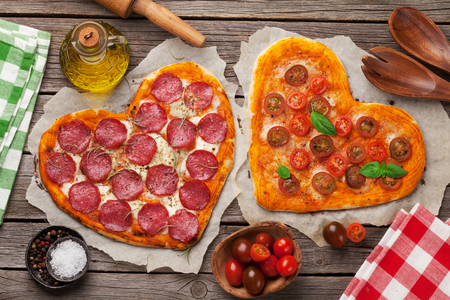 Heart shaped pizza with tomatoes and mozzarella and pepperoni. Valentines day greeting card. Top view