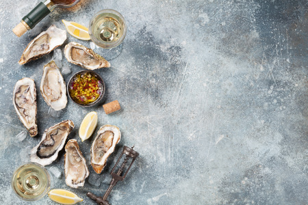 Fresh oysters and white wine on stone table. Top view with space for your text