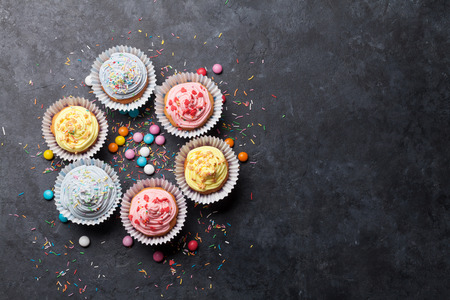 Sweet cupcakes with colorful decor and candies. Top view with space for your greetings Stok Fotoğraf