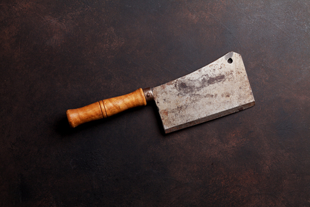 Butcher. Vintage meat knife over stone table. Top view