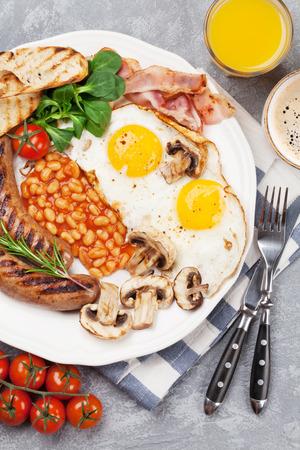 Englisches Frühstück. Spiegeleier, Würstchen, Speck, Bohnen, Toast, Tomaten, Orangensaft und Kaffeetasse Standard-Bild - 98590994