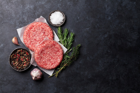 Raw minced meat and ingredients for home made grill burgers cooking with spaces and herbs. Top view with space for your text