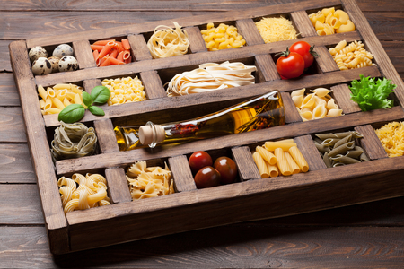 Various pasta in wooden box. Cooking concept