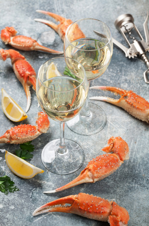 Seafood and wine. Lobster with lemon and white wine glasses. On stone table