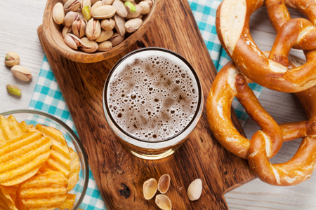Lager beer and snacks on wooden table. Nuts, chips, pretzel. Top view
