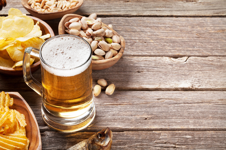 Lager beer mug and snacks on wooden table. Nuts, chips and dry fish. With copy space