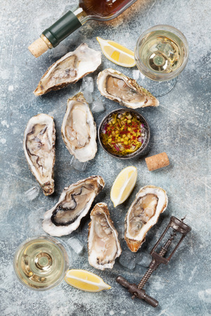 Fresh oysters and white wine on stone table. Top view