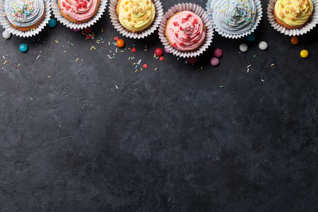 Sweet cupcakes with colorful decor and candies. Top view with space for your greetings Banque d'images