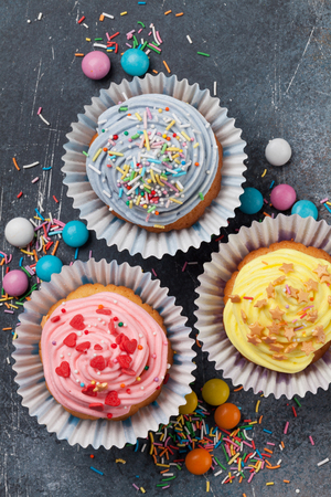 Sweet cupcakes with colorful decor and candies. Top view Banco de Imagens