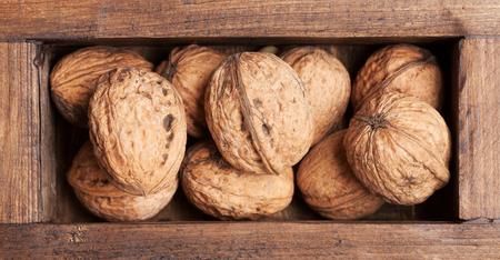 Walnut nuts in wooden box. Top view Zdjęcie Seryjne