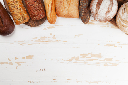 Various crusty bread and buns on white wooden background. Top view with space for your text