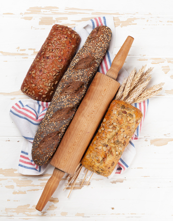 Various crusty bread and buns on white wooden background. Top view