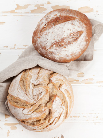 Various crusty homemade bread on white wooden background. Top view Фото со стока