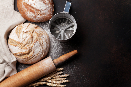Various crusty bread and buns on blackboard background. Top view with space for your text