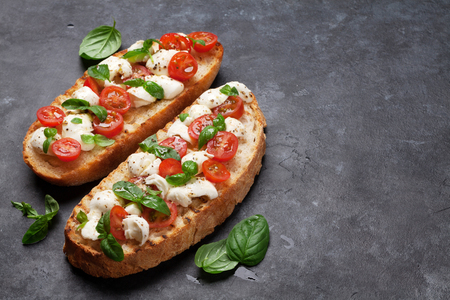 Caprese bruschetta toasts with mozzarella, cherry tomatoes and fresh garden basil. With space for your text Stock Photo