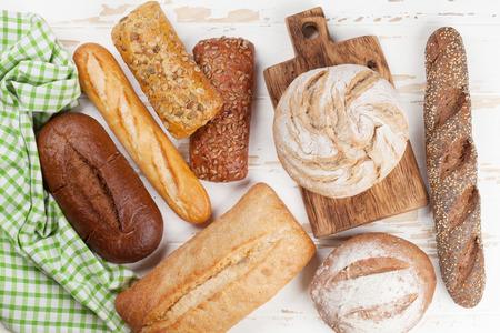 Różnorodny skorupiasty chleb i babeczki na białym drewnianym stole. Widok z góry