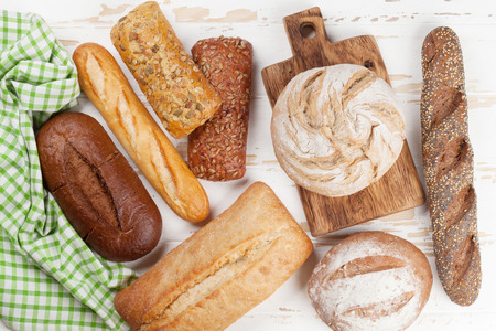 Various crusty bread and buns on white wooden table. Top view Фото со стока - 99943588
