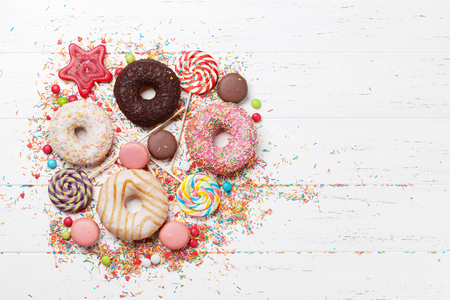 Colorful sweets. Lollipops, macaroons, candies, donuts. Top view with space for your text