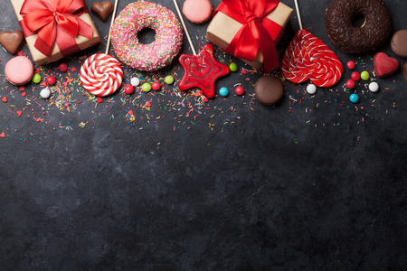 Colorful sweets. Lollipops, macaroons, candies, donuts and gift boxes. Top view with space for your text Stockfoto