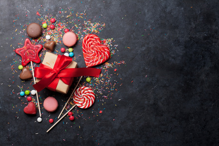 Colorful sweets. Lollipops, macaroons, candies and gift box. Top view with space for your text Stockfoto