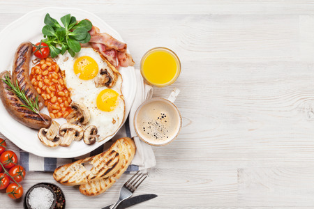 English breakfast. Fried eggs, sausages, bacon, beans, toasts, tomatoes, orange juice and coffee cup on wooden table. Top view with copy space Standard-Bild - 100019985