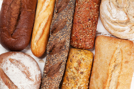 Various crusty bread and buns on white wooden table. Top view Stock fotó - 100669398