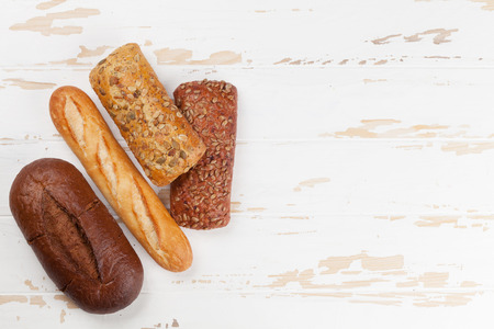 Various crusty bread and buns on white wooden table. Top view with space for your text Stock Photo