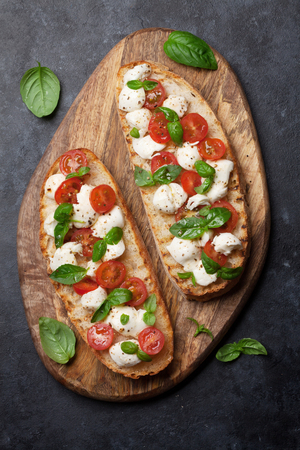 Caprese bruschetta toasts with cherry tomatoes, mozzarella and basil. Top view Banque d'images - 100806975