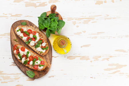 Caprese bruschetta toasts with cherry tomatoes, mozzarella and basil. Top view with space for your text Banque d'images - 100806996
