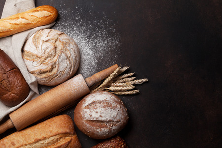 Homemade crusty bread cooking on blackboard background. Top view with space for your text
