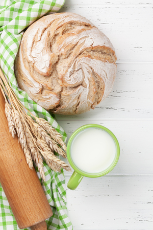 Homemade crusty bread and cup of milk on wooden background. Top view