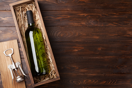 White wine bottle in box on wooden table. Top view with copy space