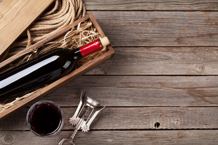 Red wine bottle and glass on wooden table. Top view with copy space Stock Photo