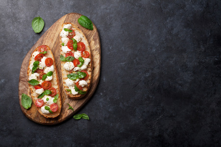 Caprese bruschetta toasts with cherry tomatoes, mozzarella and basil. Top view with space for your text