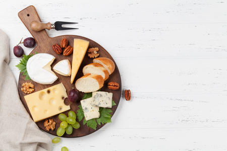 Cheese plate with grapes and nuts. Wine snaks. Top view with space for your text