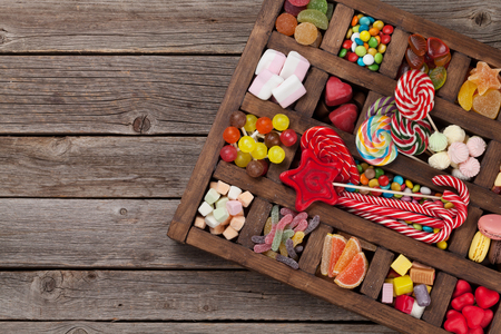 Colorful sweets box. Lollipops, macaroons, marshmallow, marmalade and candies. Top view with space for your greetings 免版税图像