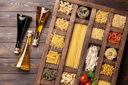 Various pasta in wooden box and condiments. Cooking concept. Top view