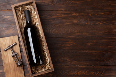 Red wine bottle in box on wooden table. Top view with space for your text