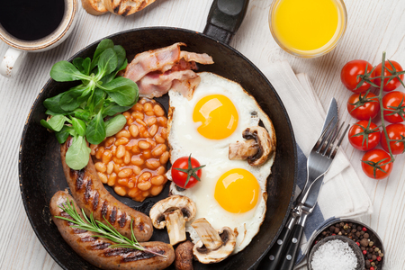 English breakfast. Fried eggs, sausages, bacon, beans, toasts, tomatoes, orange juice and coffee cup on wooden table. Top view Standard-Bild - 102309163
